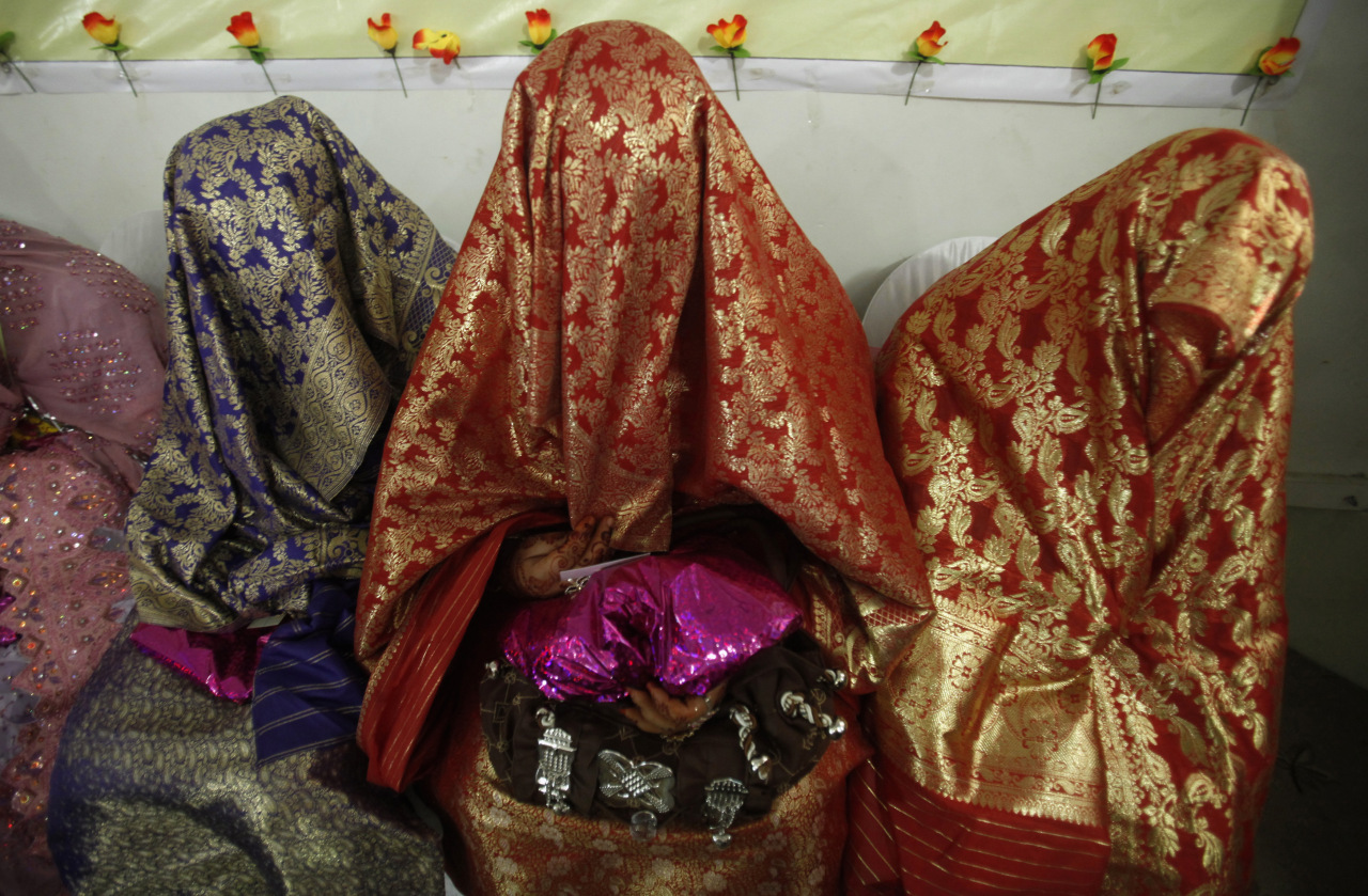 Brides sit together during a mass wedding ceremony in Peshawar
